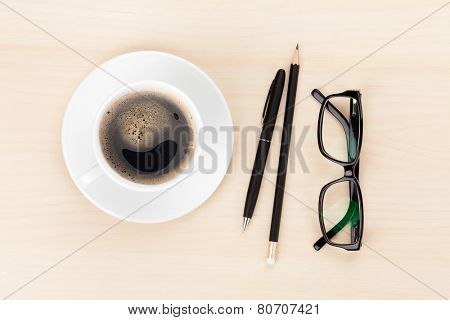 Office desk with coffee cup, supplies and glasses. View from above