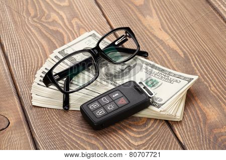 Money cash, glasses and car remote key on wooden table