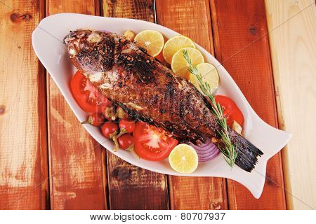 main course: whole fryed sunfish on wooden table with lemons and peppers