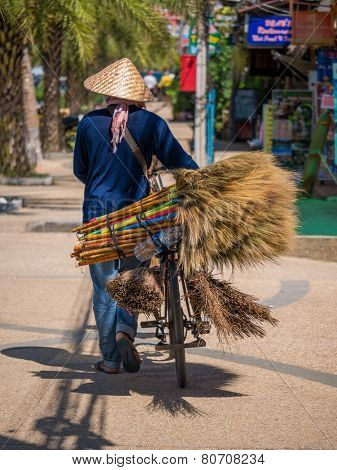 Unknown Street vendor of traditional made brooms.Street vending is very common in Thailand and also a main tourist attraction.