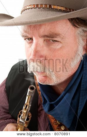 Cowboy Blowing On The End Of A Hot Pistol