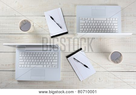 High angle shot of two computer work stations back-to-back with almost identical layouts. Horizontal format on a whitewashed wood table.