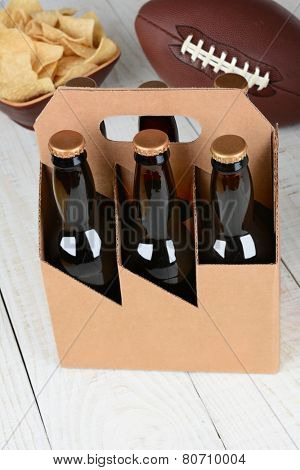 High angle shot of a six pack of beer bottles a bowl of chips and an American football. Vertical format with focus on the beer bottles. Bottles have no labels and the carrier is blank.
