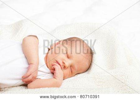 Newborn baby girl sleeping on a white blanket