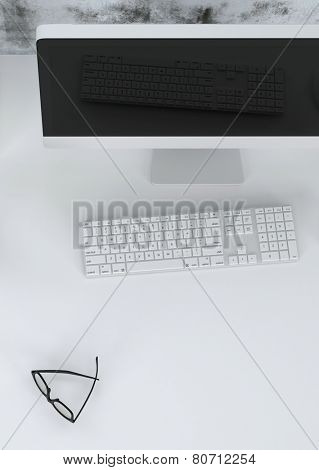 3D Rendering of Close up high angle view of a modern workstation in an office or study with a desktop computer, keyboard and spectacles on a light grey desk