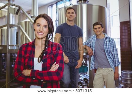 Casual happy stylish team smiling at camera together in the factory