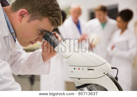 Young medical student working with microscope at the university