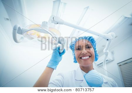 Low angle portrait of smiling female dentist adjusting light