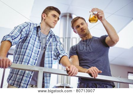 Men holding beaker with beer in the factory