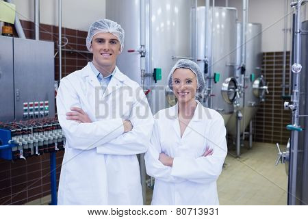 Happy scientists posing with arms crossed in the factory