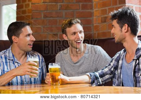 Happy friends toasting with pints of beer in a bar
