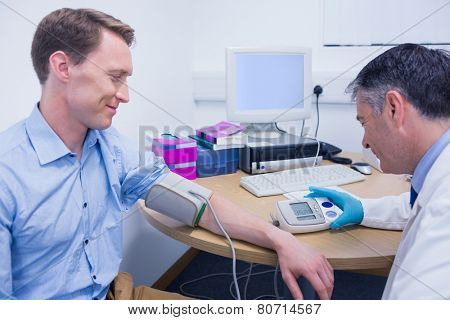 Doctor measuring his patients blood pressure at the hospital