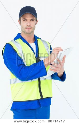 Portrait of confident supervisor writing notes on clipboard over white background