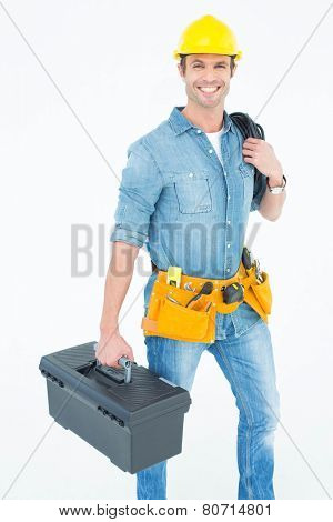 Portrait of happy electrician with tool box and wire against white background