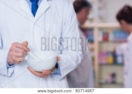 Close up of a pharmacist using mortar and pestle in the pharmacy