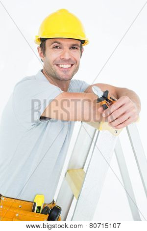 Portrait of technician holding pliers while leaning on step ladder over white background