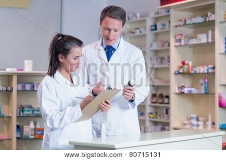 Trainee holding a prescription while talking to the pharmacist in the pharmacy