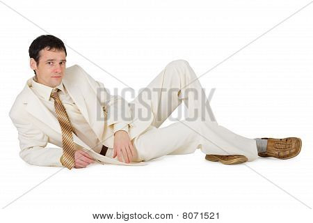 Handsome Young Man In Suit Lying On White
