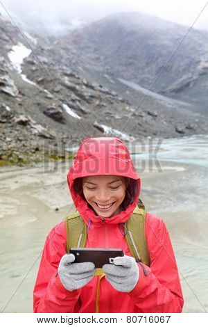 Smart phone woman texting sms using app on smartphone with touchscreen gloves. Happy hiker with mobile phone outside in nature in rain. Girl with glove of conductive fabric for touch screen.