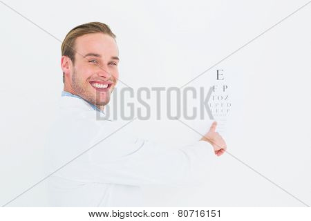 Smiling optician pointing eye test on white background