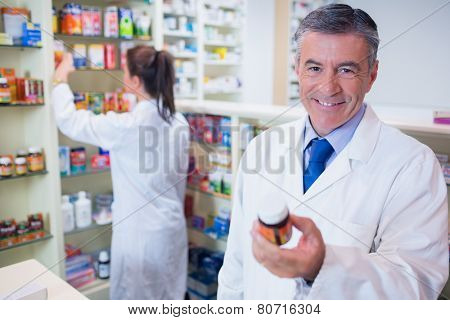 Smiling pharmacist holding a box of pills in the pharmacy