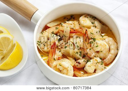 Shrimp with garlic butter, lemon and chives, in white serving pan.