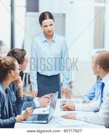 business, technology, people and management concept - strict female boss talking to business team in office