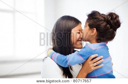 family, children and happy people concept - happy little girl hugging and kissing her mother over white room background