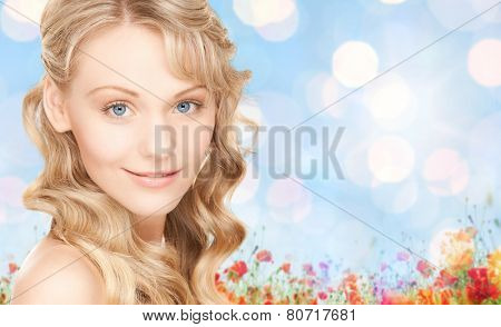 people, beauty, body and skin care concept - beautiful woman face and hands over poppy field and blue lights background