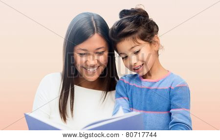 family, children, education, school and happy people concept - happy mother and daughter reading book over pink background