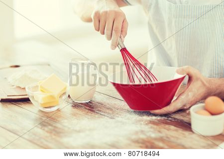 cooking and home concept - close up of male hand whisking something in a bowl