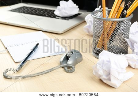 Working mess with crumpled paper and notebook on wooden table background