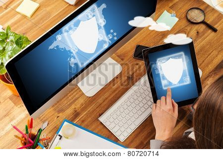 Woman working with tablet and pc placed on wooden desk with digital scheme of security. Shot from aerial view