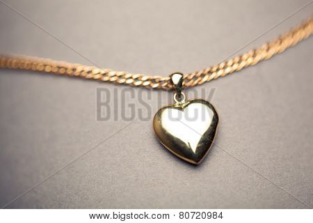 gold heart pendant on grey background