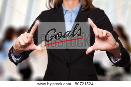 Businesswoman holds Goals sign - business concept
