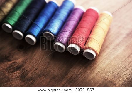 Colored sewing threads on a old work table with impressional feel.