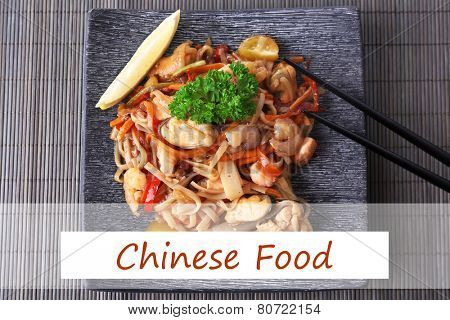 Chinese noodles with vegetables on plate on bamboo mat background and space for your text