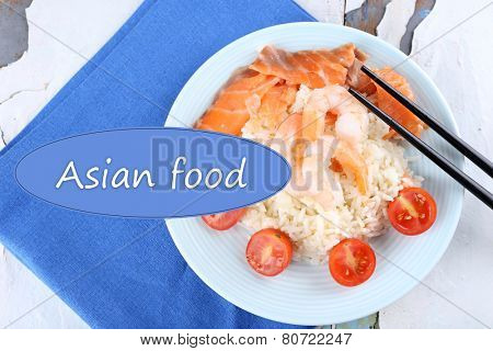 Boiled rice with shrimps and salmon on plate and space for your text