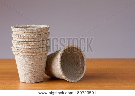 Small peat flowerpots on a wooden table
