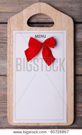 Cutting board with Menu sheet of paper on rustic wooden surface background