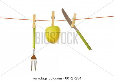 Fork, knife and apple hanging from clothesline isolated on white background