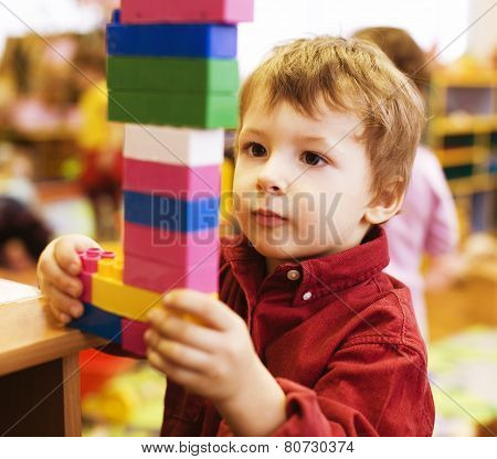 portrait of little cute  real boy making towel with lego
