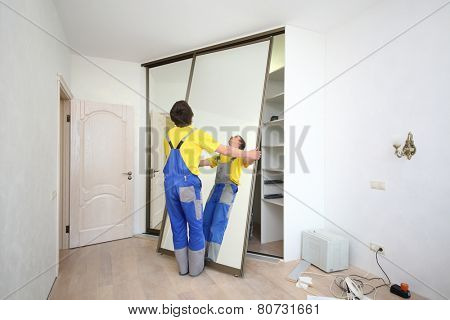 Worker setting mirrored doors on corner sliding wardrobe in room