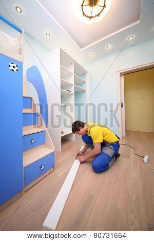 Young man sitting on the floor secures door sliding wardrobe in room with blue walls