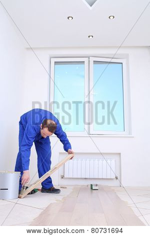 Master applies glue to floorboard with spatula in white room