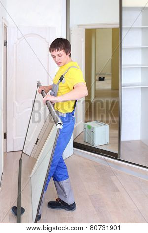 Young worker holding mirrored door on sliding wardrobe in room