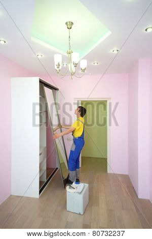 Worker setting mirrored doors for sliding wardrobe in room with pink walls