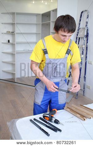 Man holding a fastening for doors sliding wardrobe