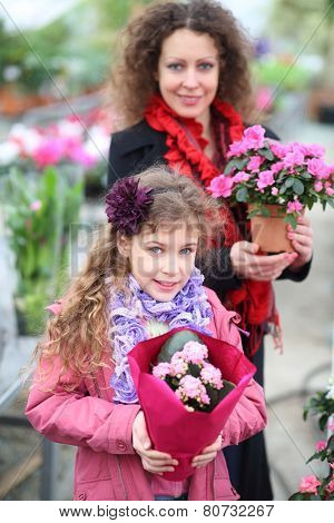 Little girl with mother holding pot with beauty flowers in the greenhouse