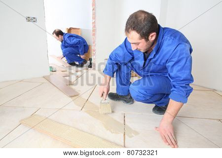 Two workers in blue overalls laid laminate in white room and hallway